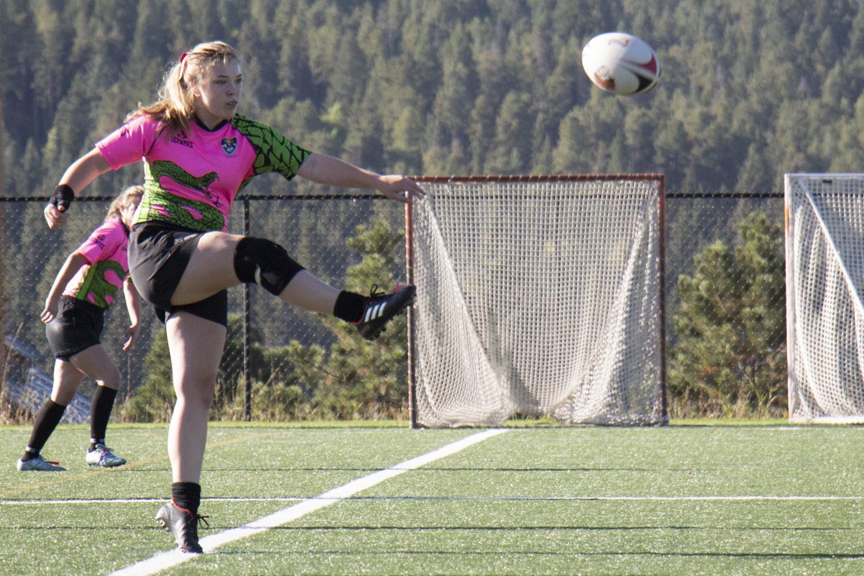 Ella Wilson, 11 dropkicks the ball during kick off.